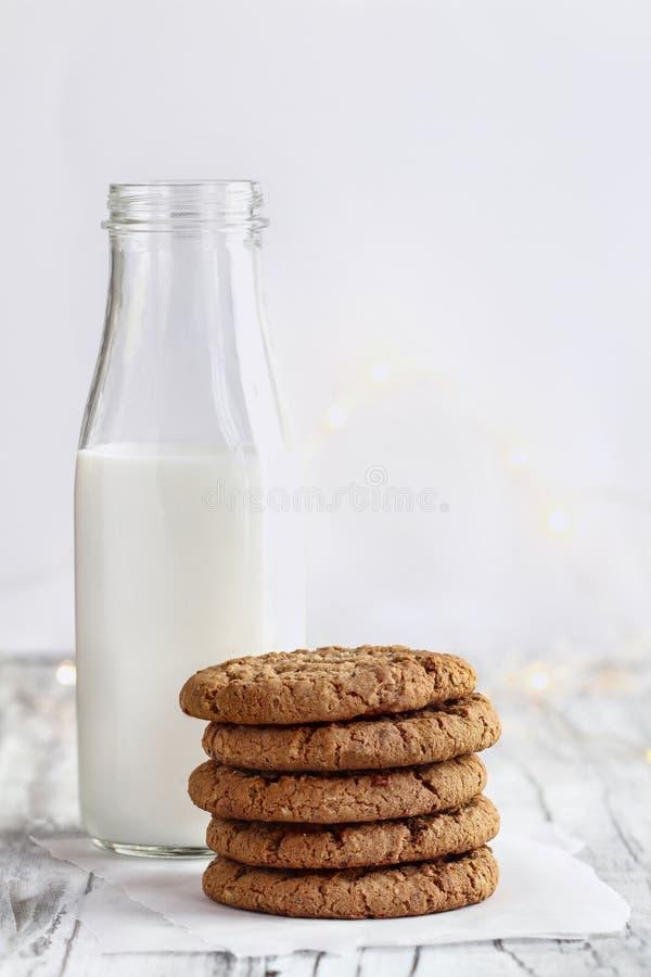 Σωρός Oatmeal των μπισκότων με το μπουκάλι του γάλακτος στοκ φωτογραφία
