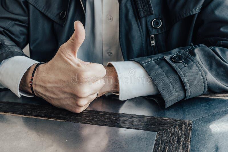 Σωστό αρσενικό χέρι με rosary στον καρπό και ένας αντίχειρας που αυξάνεται επάνω E στοκ εικόνες