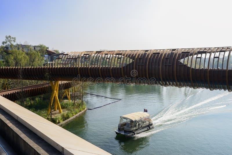 Σωλήνας-διαμορφωμένη ξύλινη γέφυρα για πεζούς πέρα από το νερό το ηλιόλουστο χειμερινό μεσημέρι στοκ φωτογραφία