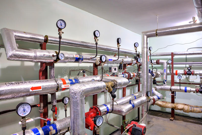 Σωλήνες του ζεστού νερού και της θέρμανσης με τις συσκευές ελέγχου στοκ φωτογραφία με δικαίωμα ελεύθερης χρήσης