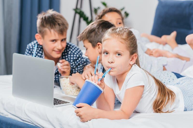 σόδα κατανάλωσης μικρών κοριτσιών ενώ φίλοι που χρησιμοποιούν το lap-top στοκ φωτογραφία με δικαίωμα ελεύθερης χρήσης