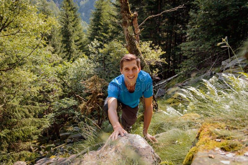 Σόλο άτομο που αναρριχείται σε έναν βράχο στο δάσος στοκ εικόνες