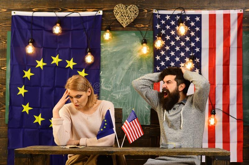 Σύγκρουση μεταξύ της ευρωπαϊκής ένωσης των ΗΠΑ και σύγκρουση του άνδρα και της γυναίκας με τη σημαία των ΗΠΑ και της ΕΕ στοκ φωτογραφία με δικαίωμα ελεύθερης χρήσης