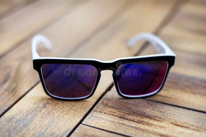 Σύγχρονα άσπρα γυαλιά ήλιων με τα γυαλιά καθρεφτών που απομονώνονται σε ένα ξύλινο υπόβαθρο στοκ φωτογραφία