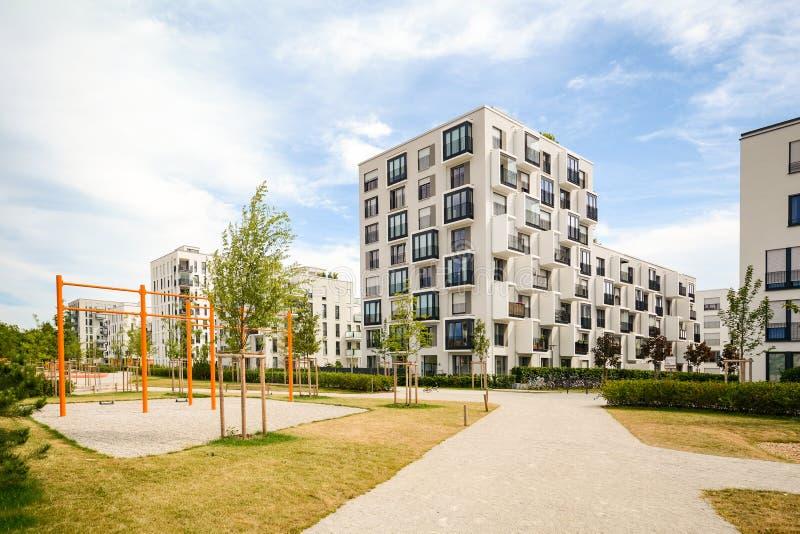 Σύγχρονα κατοικημένα κτήρια με την υπαίθρια παιδική χαρά εγκαταστάσεων και των παιδιών, πρόσοψη του νέου σπιτιού διαμερισμάτων στοκ εικόνες