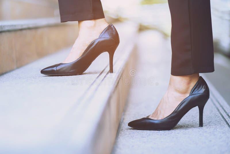 Σύγχρονα πόδια κινηματογραφήσεων σε πρώτο πλάνο εργαζόμενων γυναικών επιχειρηματιών που περπατούν επάνω τα σκαλοπάτια στοκ φωτογραφία