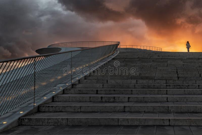 Σύγχρονα σκαλοπάτια οικοδόμησης στο στο κέντρο της πόλης της Λισσαβώνας Με το flashy ηλιοβασίλεμα και τη σκιαγραφία της γυναίκας  στοκ εικόνα