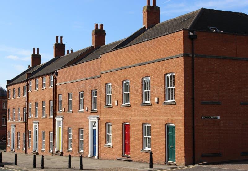 Σύγχρονα τούβλινα terraced σπίτια, ζωηρόχρωμες πόρτες στοκ εικόνες
