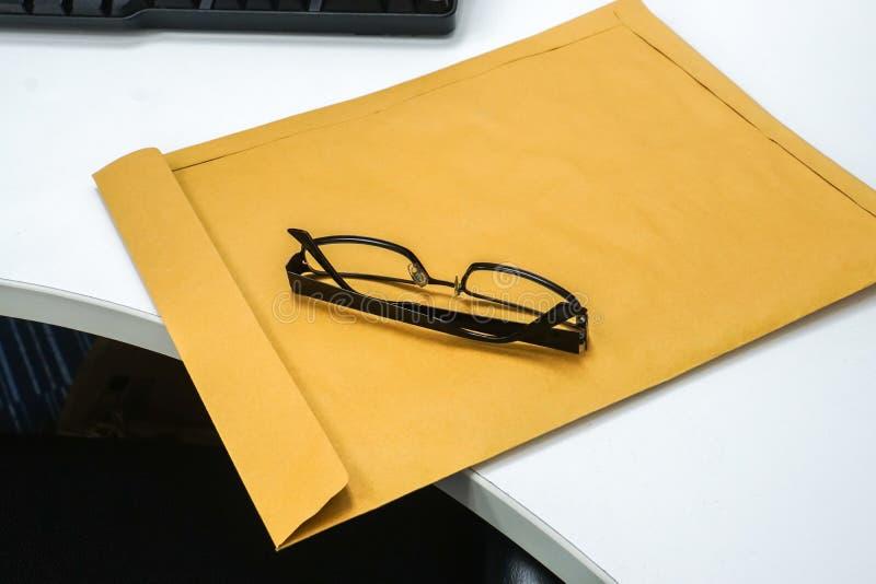Σύγχρονα eyeglasses ατόμων στον καφετή εμπιστευτικό φάκελο στοκ φωτογραφίες