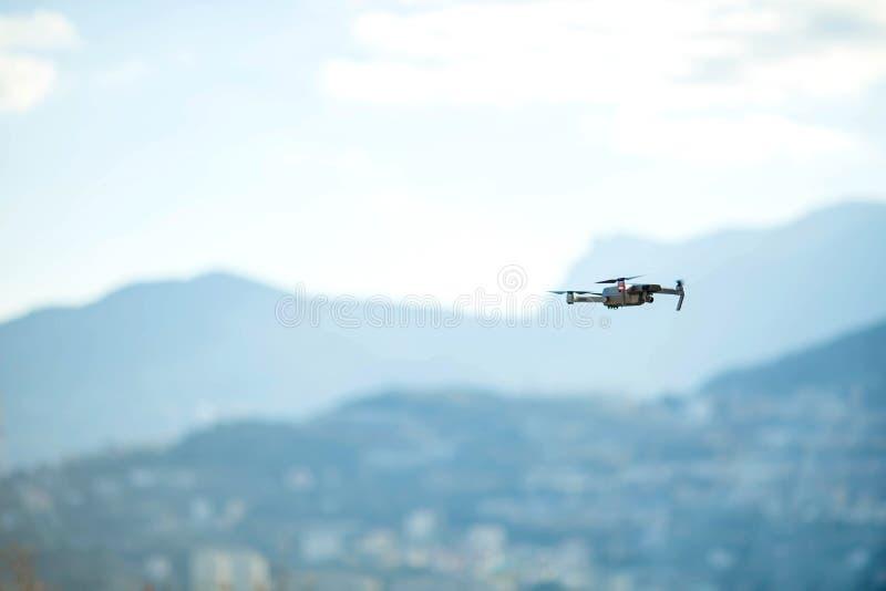 Σύγχρονες μύγες κηφήνων στα βουνά Κηφήνας στον αέρα ενάντια στο σκηνικό ενός τοπίου βουνών στοκ εικόνα