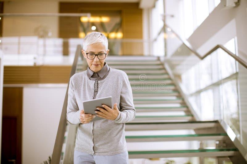Σύγχρονη ανώτερη επιχειρηματίας που χρησιμοποιεί τον υπολογιστή ταμπλετών στο γραφείο στοκ εικόνες