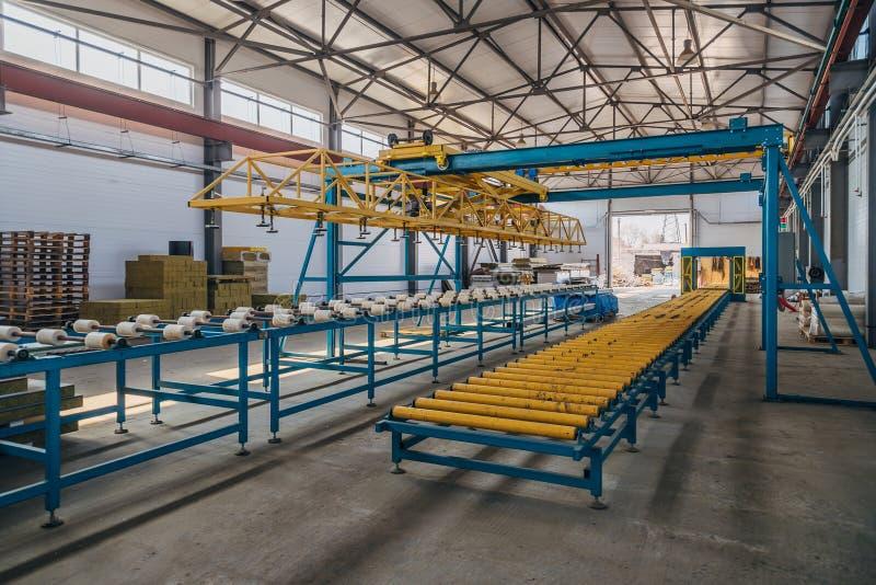 Σύγχρονη γραμμή παραγωγής επιτροπής σάντουιτς θερμικής μόνωσης Εργαλεία μηχανών, μεταφορέας κυλίνδρων και υπερυψωμένος γερανός στ στοκ εικόνα