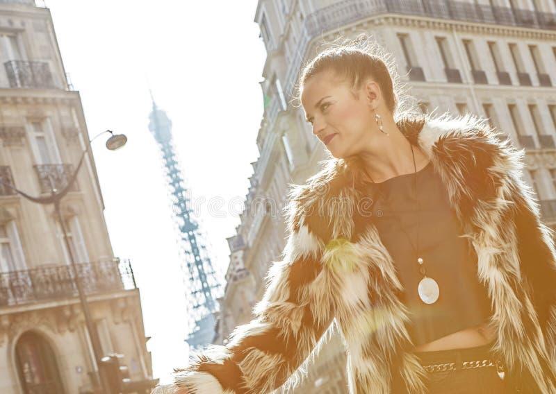 Σύγχρονη γυναίκα στο παλτό γουνών στο Παρίσι, Γαλλία που εξετάζει την απόσταση στοκ εικόνες