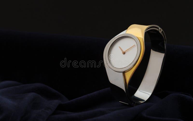Σύγχρονη γυναίκα χρυσό και ασημένιο Wristwatch στο σκοτεινό υπόβαθρο υφάσματος βελούδου στοκ φωτογραφία