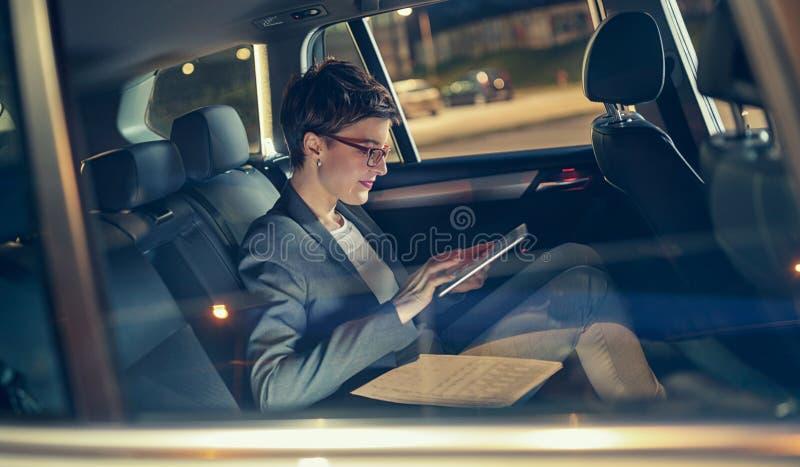 Σύγχρονη επιχειρηματίας που εργάζεται αργά στο αυτοκίνητο στοκ φωτογραφία με δικαίωμα ελεύθερης χρήσης
