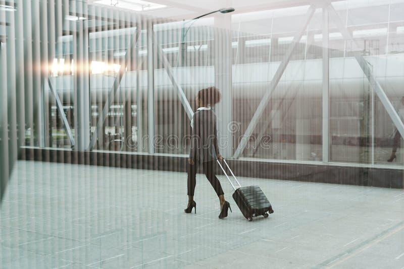 Σύγχρονη επιχειρηματίας που τραβά τη βαλίτσα της στοκ φωτογραφία
