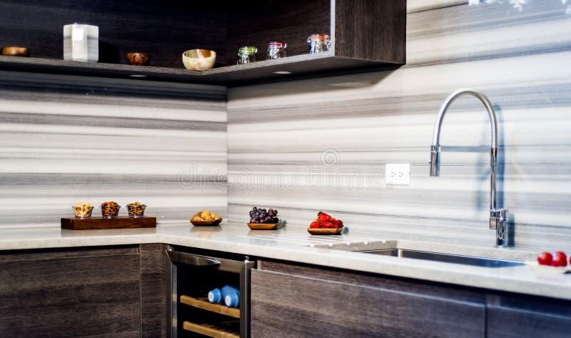 Σύγχρονη εσωτερική κουζίνα με τα καφετιά γραφεία κουζινών βάσεων και τα λευκά γραφεία κουζινών τοίχων στοκ φωτογραφία