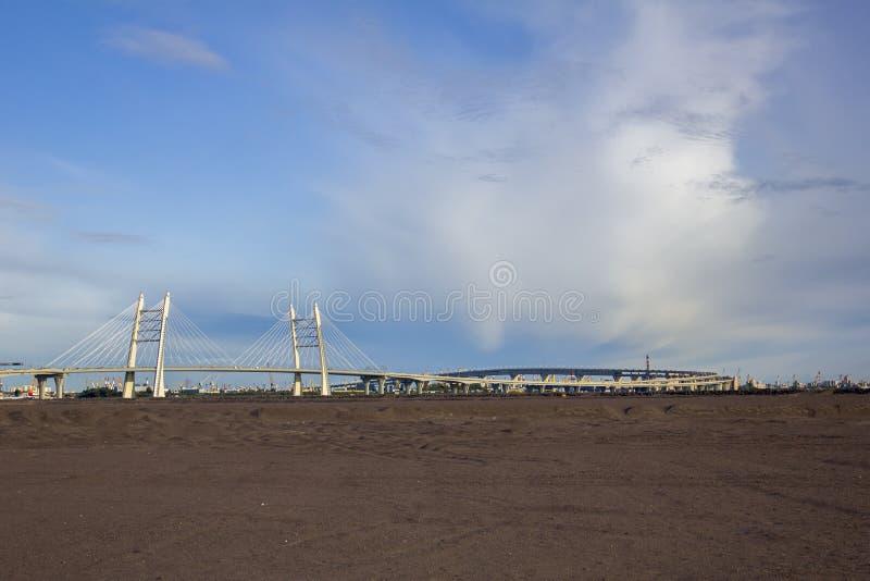 Σύγχρονη καλώδιο-μένοντη γέφυρα στο υπόβαθρο του δρόμου πέρα από την πόλη κάτω από το μπλε ουρανό, άποψη από την έρημο στοκ φωτογραφίες με δικαίωμα ελεύθερης χρήσης