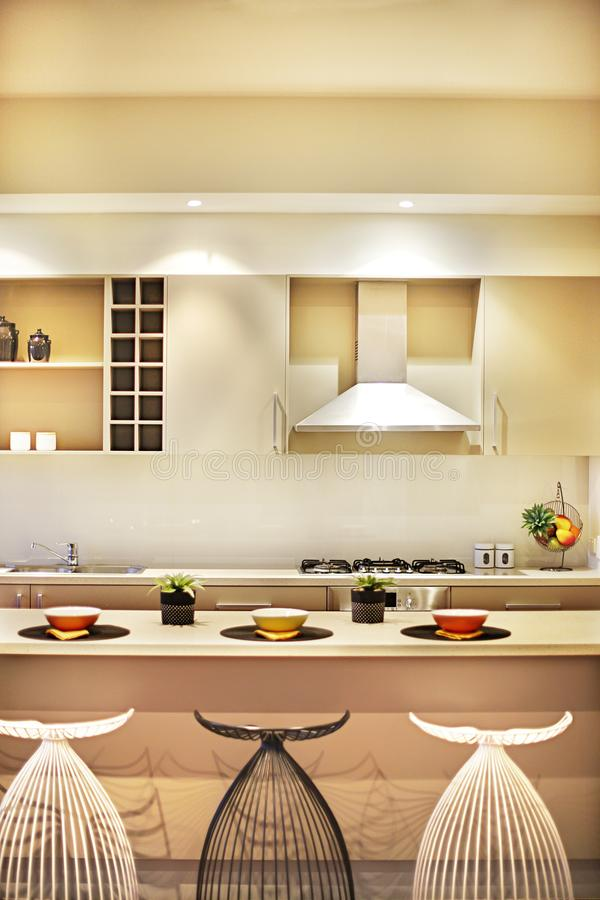 Σύγχρονη κουζίνα με τις δημιουργικές καρέκλες και την αντίθετη κορυφή στοκ φωτογραφία