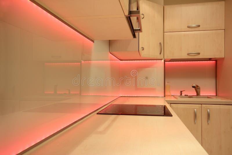 Σύγχρονη κουζίνα πολυτέλειας με το φωτισμό των κόκκινων οδηγήσεων στοκ φωτογραφία