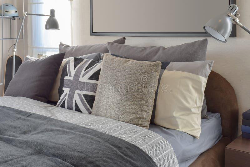 Σύγχρονη κρεβατοκάμαρα με το γκρίζο μαξιλάρι και λαμπτήρας στον ξύλινο πίνακα πλευρών στοκ εικόνα με δικαίωμα ελεύθερης χρήσης