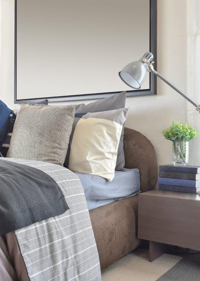 Σύγχρονη κρεβατοκάμαρα με το γκρίζο μαξιλάρι και λαμπτήρας στον ξύλινο πίνακα πλευρών στοκ εικόνες με δικαίωμα ελεύθερης χρήσης