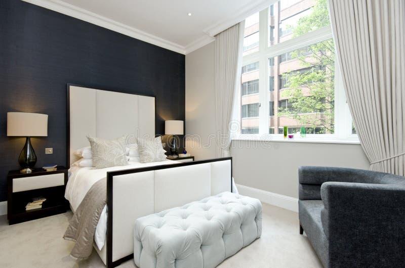 Σύγχρονη κρεβατοκάμαρα με το κρεβάτι μεγέθους βασιλιάδων με τη γούνα σχεδιαστών πολυτέλειας στοκ εικόνες