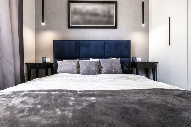 Σύγχρονη κρεβατοκάμαρα με το μπλε κρεβάτι στοκ εικόνα