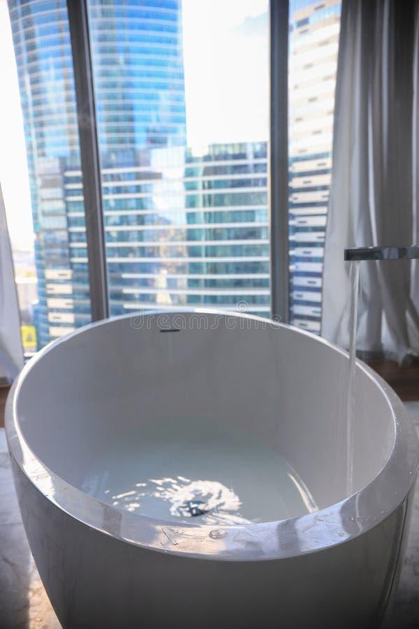 Σύγχρονη μπανιέρα πολυτέλειας στο εσωτερικό λουτρών - σύγχρονα κτήρια γυαλιού σε ένα υπόβαθρο στοκ εικόνες