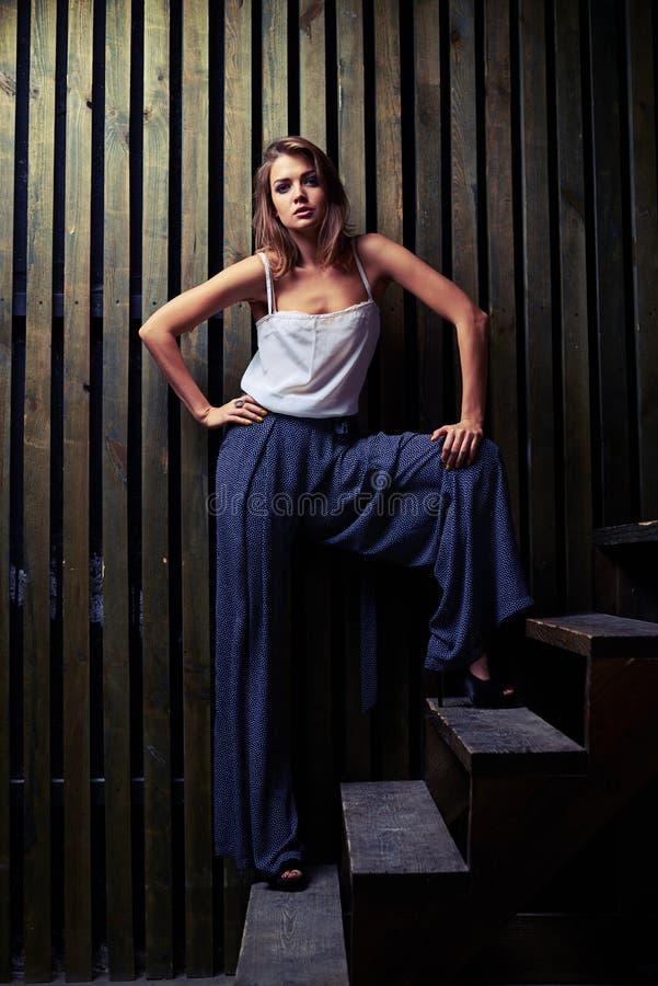 Σύγχρονη πρότυπη τοποθέτηση μόδας στην ευρεία θέση στα ξύλινα σκαλοπάτια, flo στοκ φωτογραφία με δικαίωμα ελεύθερης χρήσης