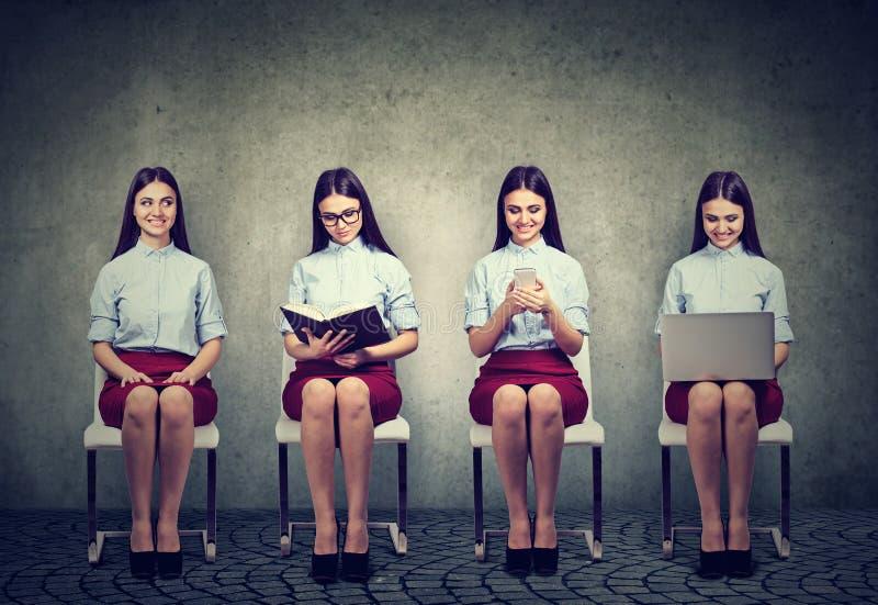 Σύγχρονη τεχνολογία εναντίον των παραδοσιακών πηγών πληροφορίας Γυναίκες με το βιβλίο, το lap-top και το κινητό τηλέφωνο στοκ εικόνες