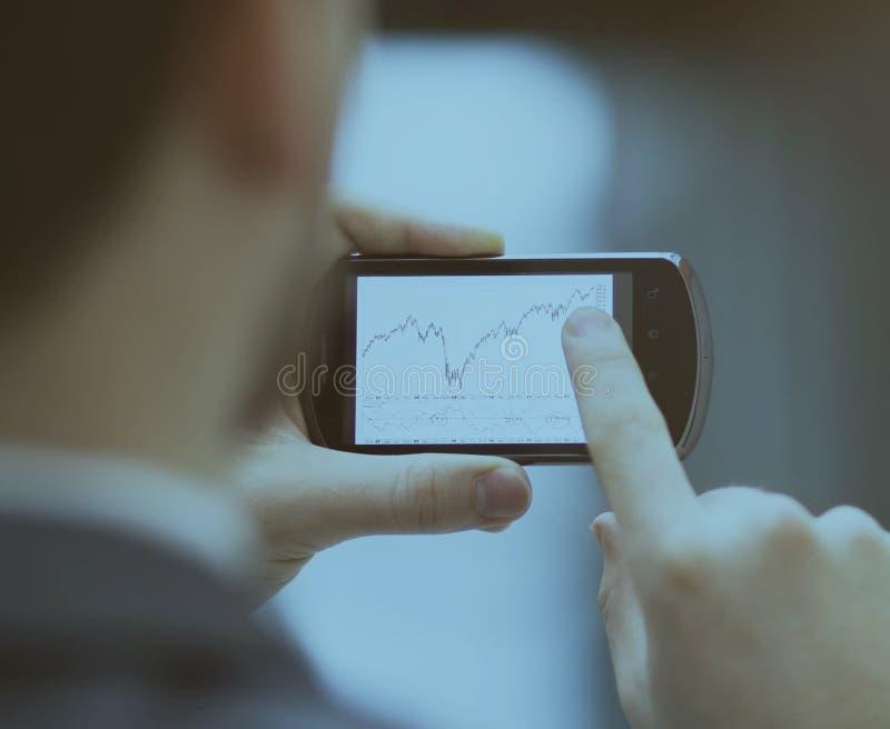 Σύγχρονοι άνθρωποι που κάνουν επιχειρήσεις, γραφικές παραστάσεις και διαγράμματα που καταδεικνύονται την οθόνη ενός τηλεφώνου στοκ φωτογραφία με δικαίωμα ελεύθερης χρήσης
