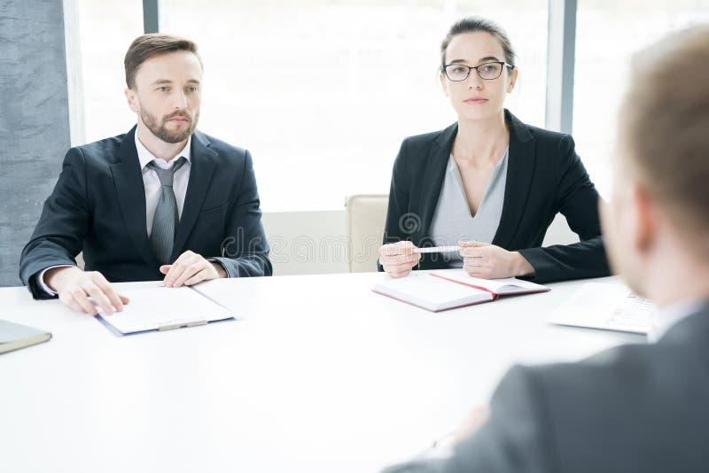 Σύγχρονοι επιχειρηματίες στον πίνακα συνεδρίασης στοκ εικόνα