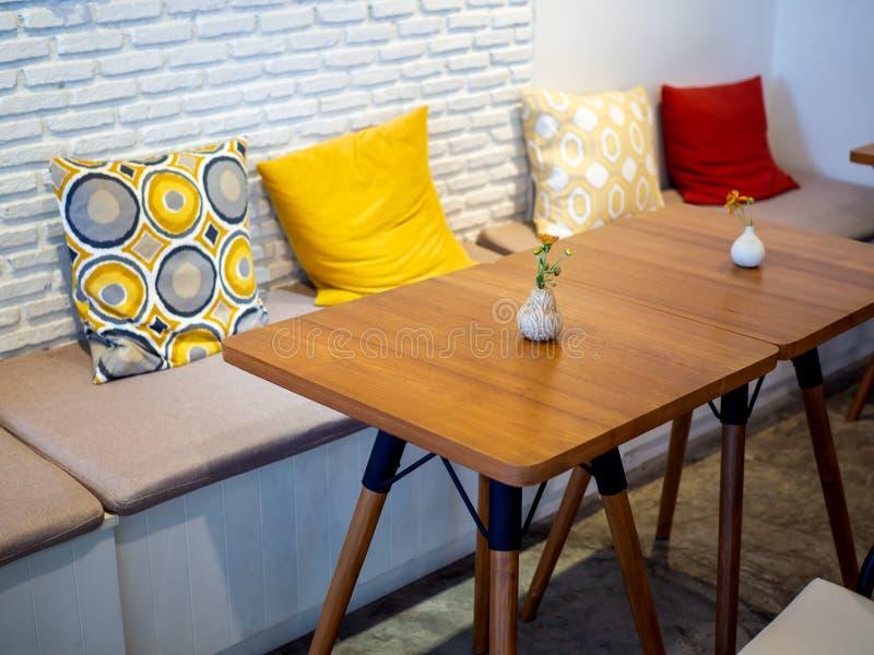 Σύγχρονοι ξύλινοι πίνακες, ζωηρόχρωμα μαξιλάρια στο άσπρο υπόβαθρο τουβλότοιχος στοκ εικόνες
