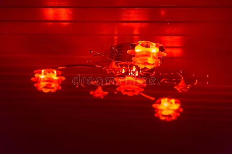 Σύγχρονος ανώτατος λαμπτήρας που διακοσμείται με τα τριαντάφυλλα, λάμποντας κόκκινο φως στο σκοτάδι, εγχώριο εσωτερικό υπόβαθρο στοκ εικόνες