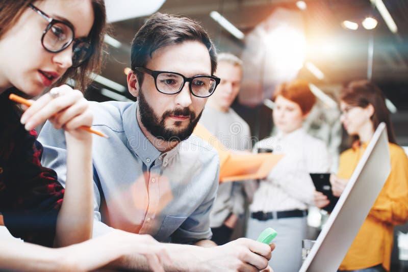 Σύγχρονος γενειοφόρος επιχειρηματίας και ο συνάδελφός του, ένα κορίτσι στα γυαλιά, που λειτουργούν σε ένα νέο πρόγραμμα πίσω από  στοκ φωτογραφία με δικαίωμα ελεύθερης χρήσης