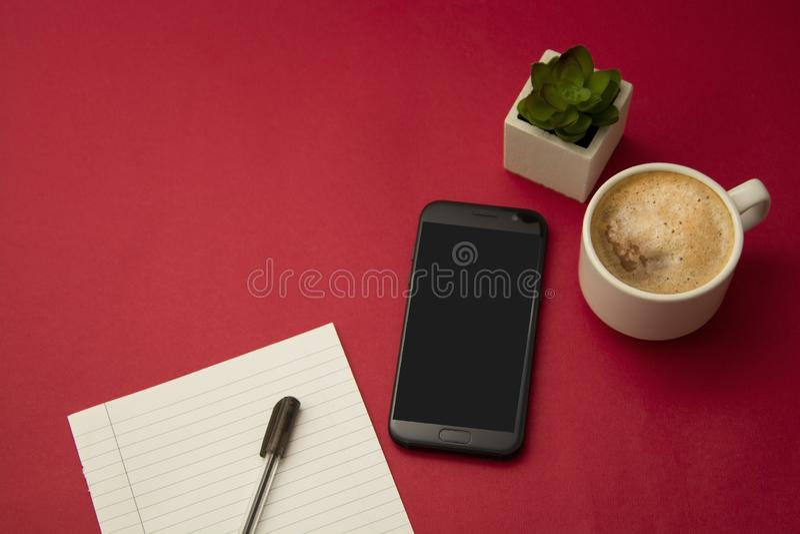 Σύγχρονος εργασιακός χώρος με το φλιτζάνι του καφέ, το smartphone, τις διακοσμητικές εγκαταστάσεις succulent και μια μάνδρα Κόκκι στοκ εικόνα