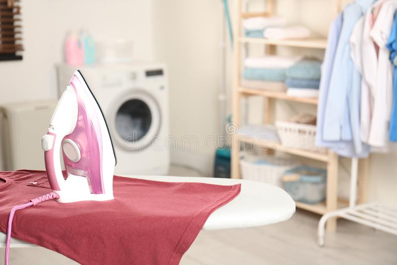 Σύγχρονος ηλεκτρικός σίδηρος και καθαρό μπλουζάκι στο πλυντήριο στοκ εικόνες με δικαίωμα ελεύθερης χρήσης