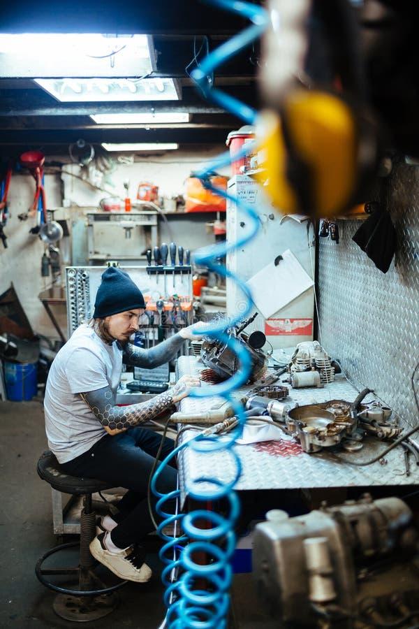Σύγχρονος μηχανικός που επισκευάζει τα μέρη στο εργαστήριο στοκ εικόνες