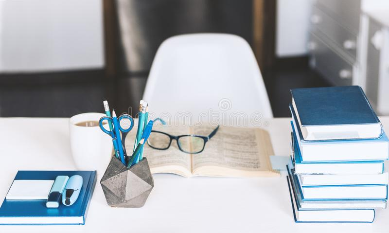Σύγχρονος μοντέρνος χώρος εργασίας γραφείων με το ανοικτό βιβλίο, γυαλιά, προμήθειες γραφείων και βιβλία, έννοια εργασίας γραφείω στοκ εικόνες