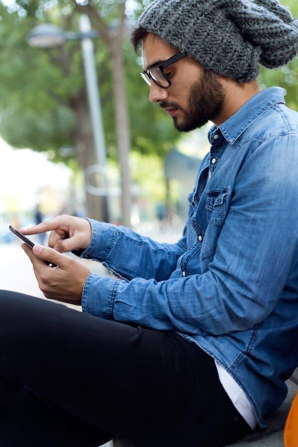 Σύγχρονος νεαρός άνδρας με το κινητό τηλέφωνο στην οδό στοκ φωτογραφία