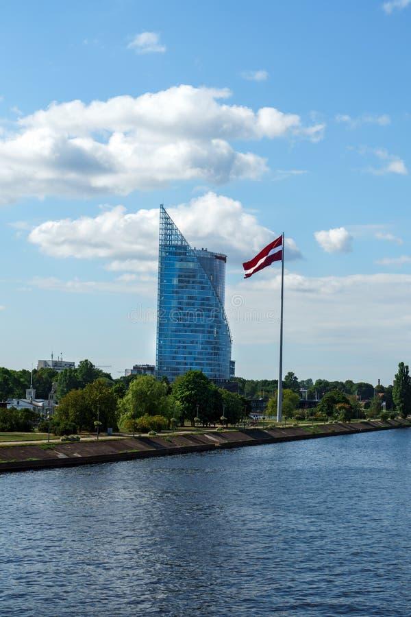 Σύγχρονος ουρανοξύστης γυαλιού του γραφείου Swedbank και της λετονικής σημαίας ενάντια στο μπλε ουρανό στην πόλη της Ρήγας, Λετον στοκ εικόνα