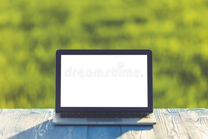 Σύγχρονος φορητός προσωπικός υπολογιστής στον ξύλινο πίνακα και την άποψη του πράσινου τομέα στοκ εικόνα