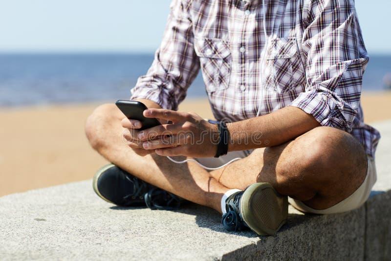 Σύγχρονο άτομο που χρησιμοποιεί Smartphone στην παραλία στοκ εικόνες
