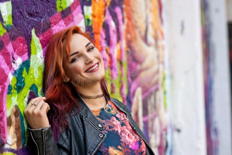 Σύγχρονο αστικό κορίτσι μπροστά από τον τοίχο γκράφιτι στοκ εικόνα