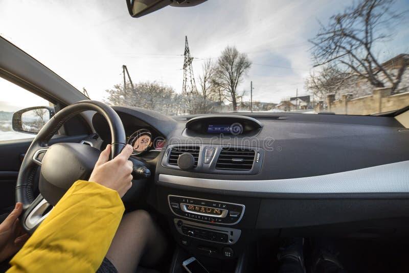 Σύγχρονο εσωτερικό αυτοκινήτων με τα θηλυκά χέρια οδηγών στο τιμόνι, χειμερινό χιονώδες τοπίο έξω Ασφαλής οδηγώντας έννοια στοκ φωτογραφία με δικαίωμα ελεύθερης χρήσης