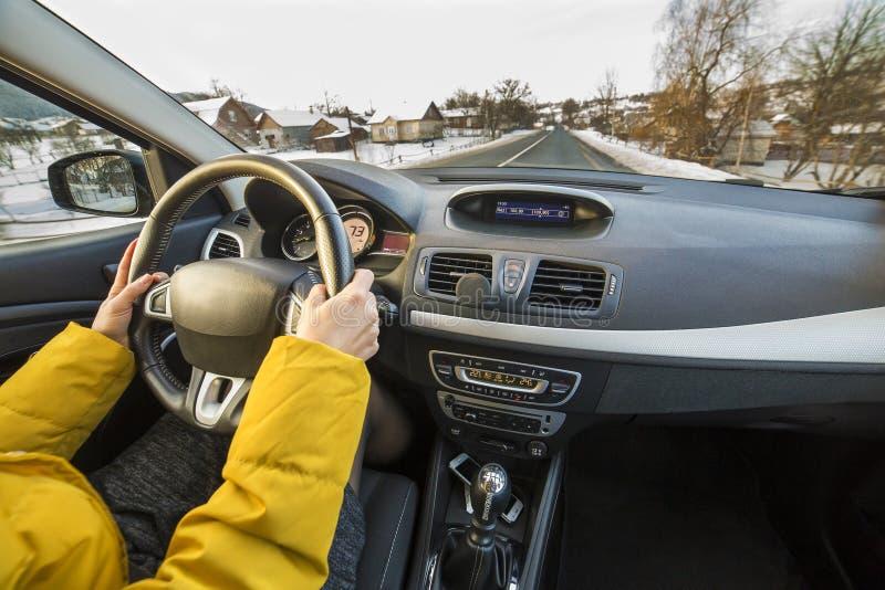Σύγχρονο εσωτερικό αυτοκινήτων με τα θηλυκά χέρια οδηγών στο τιμόνι, χειμερινό χιονώδες τοπίο έξω Ασφαλής οδηγώντας έννοια στοκ εικόνες
