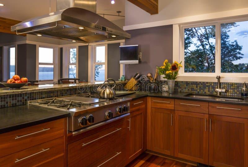 Σύγχρονο εσωτερικό εγχώριων κουζινών upscale με τα ξύλινα γραφεία, τη σόμπα αερίου, την κουκούλα διεξόδων και τα παράθυρα άποψης στοκ εικόνα