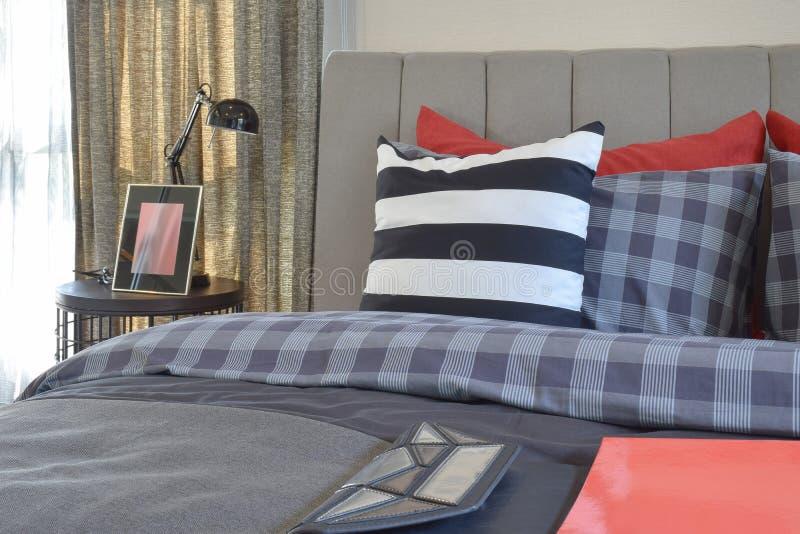 Σύγχρονο εσωτερικό κρεβατοκάμαρων με το ριγωτό μαξιλάρι στον επιτραπέζιο λαμπτήρα κρεβατιών και πλευρών στοκ εικόνες