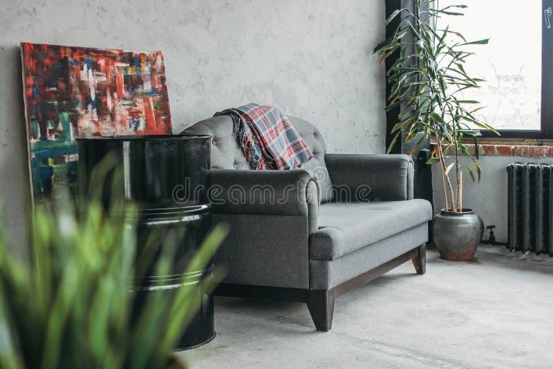 Σύγχρονο εσωτερικό σοφιτών eco στο καθιστικό, τσιμεντένιο πάτωμα, καναπές, στούντιο μινιμαλισμού στοκ εικόνες με δικαίωμα ελεύθερης χρήσης